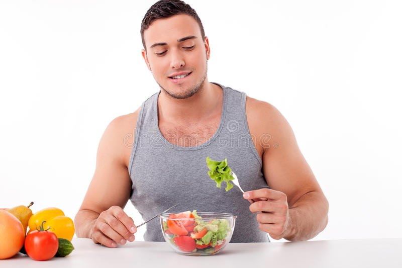 handsome-young-man-eating-healthy-food-cheerful-fit-guy-sitting-table-tasting-salad-looking-fork-57712937